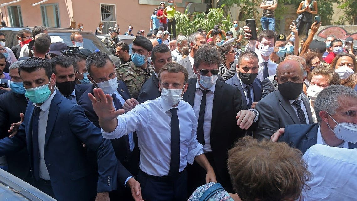 French President Emmanuel Macron greets people as he visits the Gemmayzeh neighborhood. (AFP)