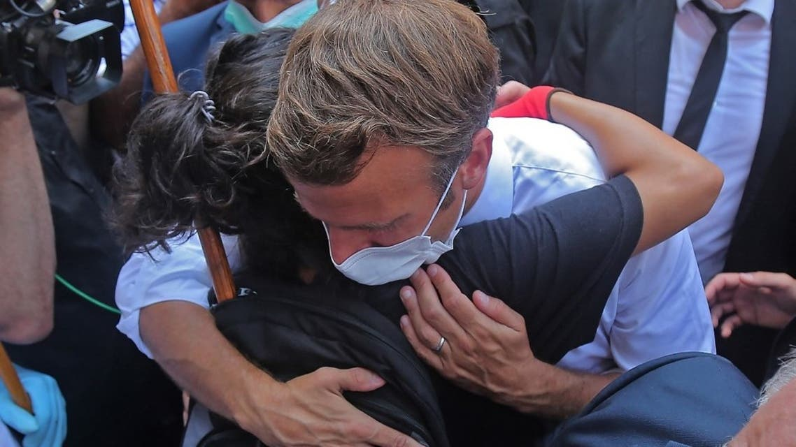 A Lebanese youth hugs French President Emmanuel Macron during a visit to the Gemmayzeh neighbourhood, which has suffered extensive damage due to a massive explosion in the Lebanese capital, on August 6, 2020. (AFP)