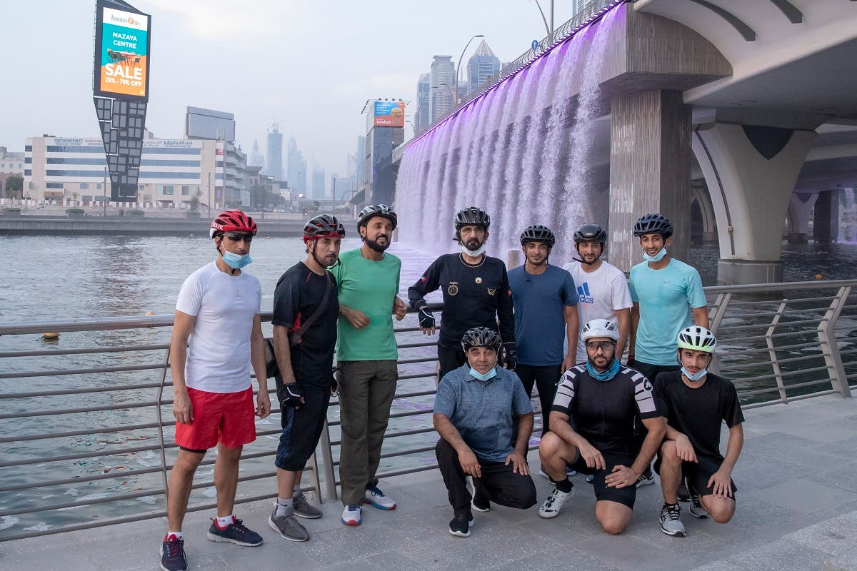 Sheikh Mohammed and associates get down from their bikes for a group photo at Dubai Canal. (Dubai Media Office)