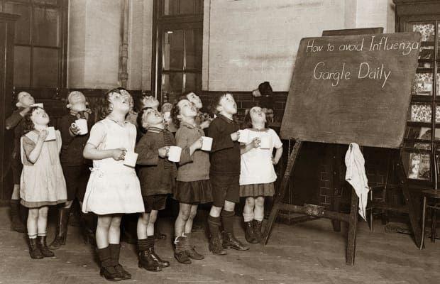 صورة لأطفال حصلوا على تعليمات طبية بممارسة الغرغرة بالماء باحدى المدارس زمن الأنفلونزا