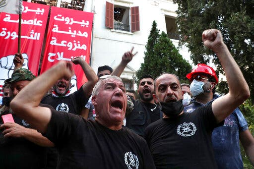 Retired army officers chant slogans inside the Lebanese foreign ministry in Beirut, Lebanon, Saturday, Aug. 8, 2020. (AP)