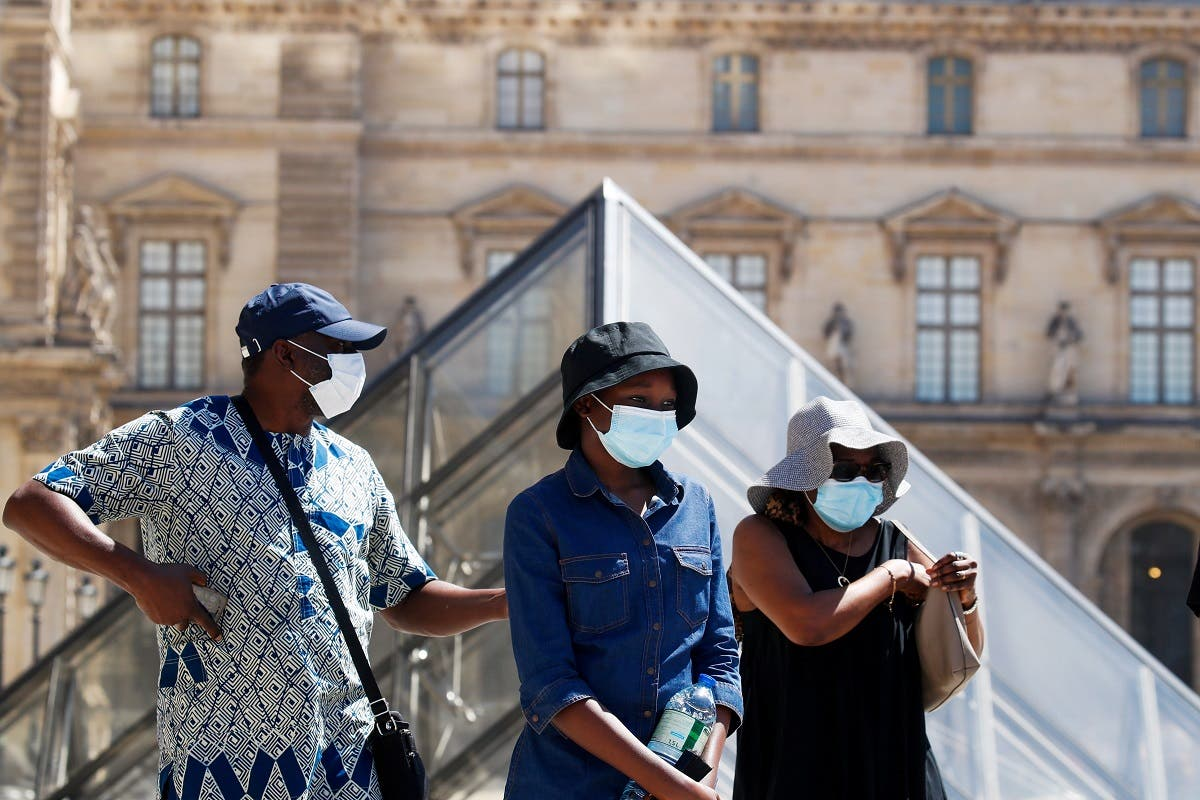People wearing protective masks walk near the Louvre Museum as France reinforces mask-wearing as part of efforts to curb a resurgence of coronavirus across the country, in Paris, France, on August 6, 2020. (Reuters)