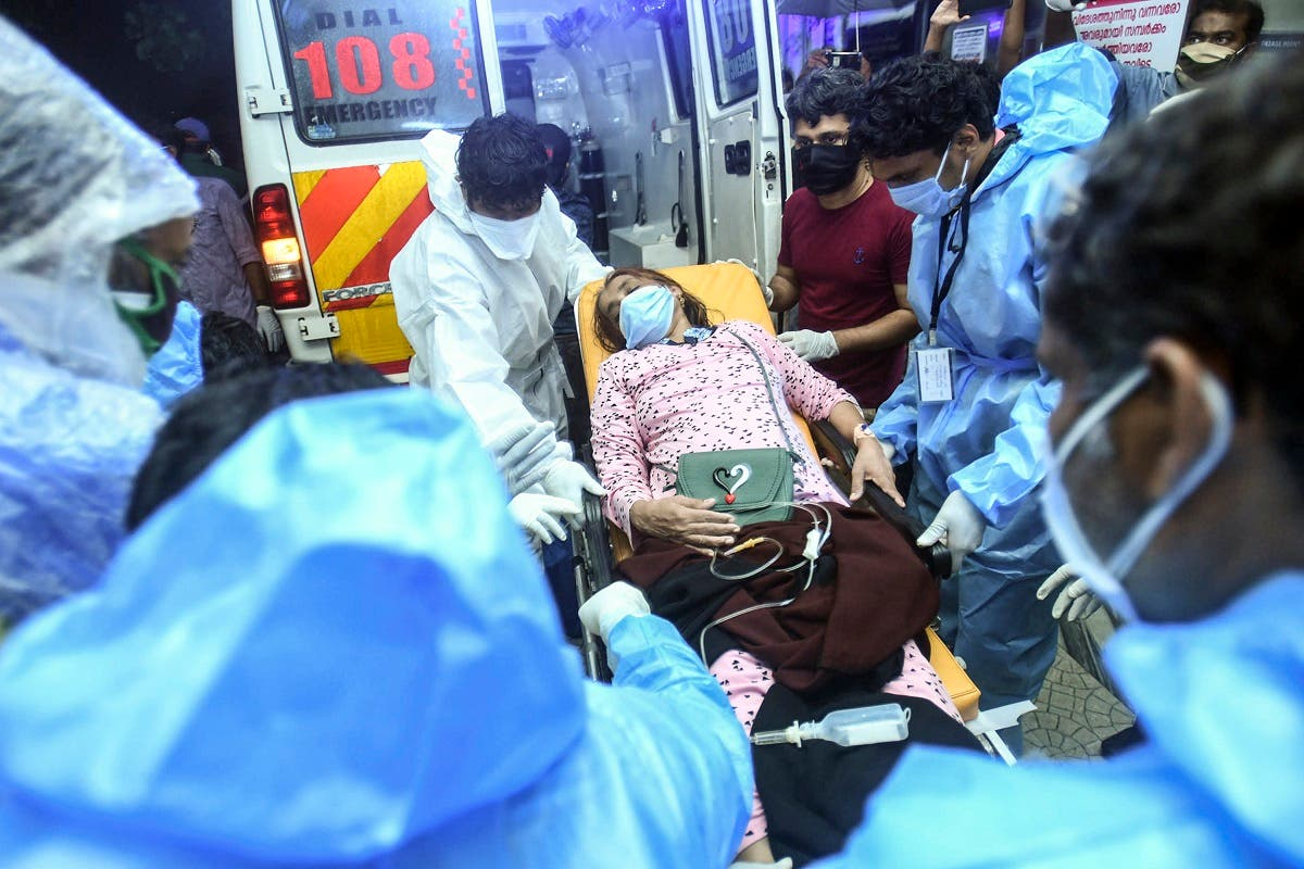 Health workers transfer an injured passenger on a stretcher to take her to a hospital in Kozhikode, Kerala, after the Air India Express crashed at Calicut International Airport, on August 7, 2020. (AFP)