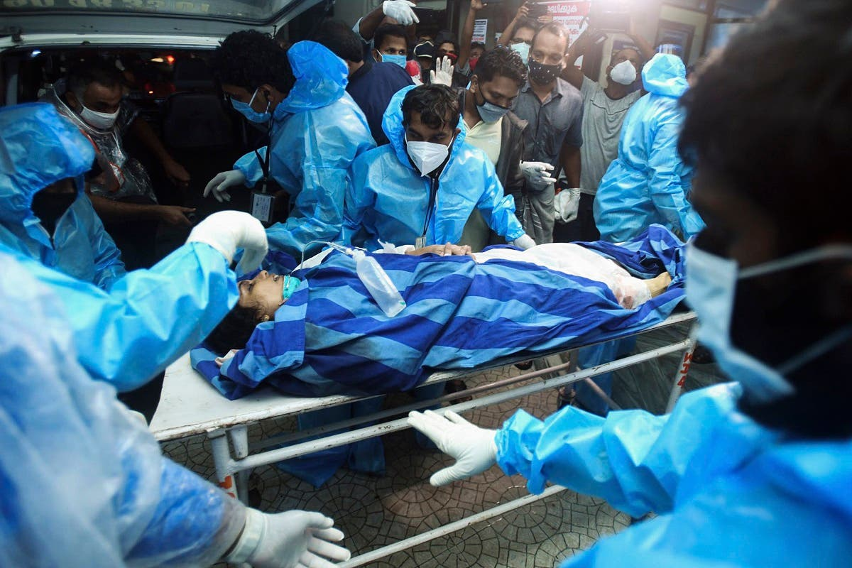 Health workers transfer an injured passenger on a stretcher to take her inside a hospital in Kozhikode, Kerala, after an Air India Express jet crashed by overshooting the runway at Calicut International Airport, on August 7, 2020. (AFP)