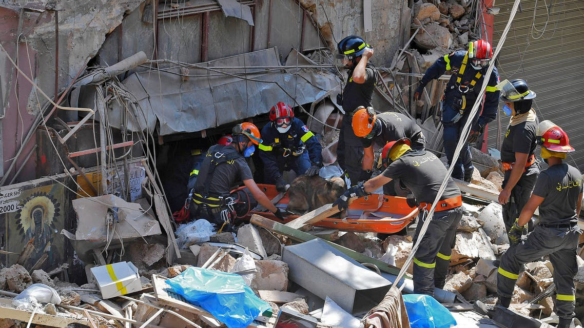 Members of the Lebanese civil defence use a dog to search for victims and survivors under the rubble of a building in the Gemayzeh neighbourhood. (AFP)