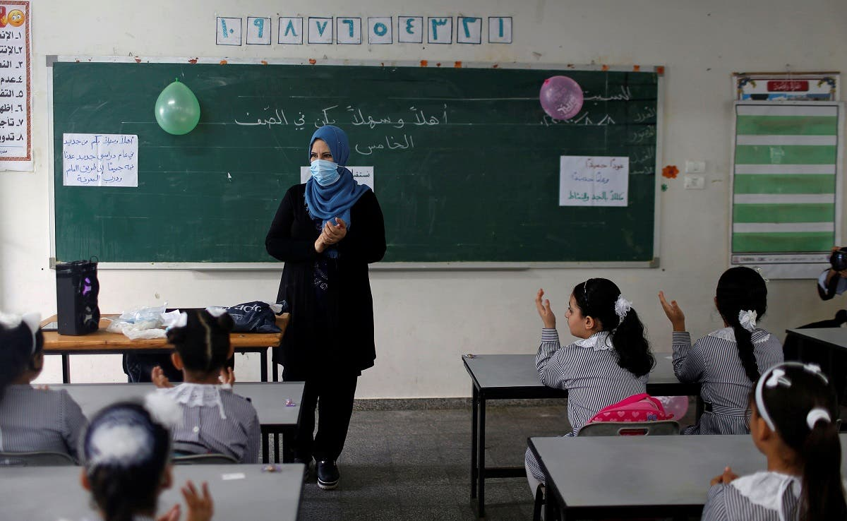 ce mask gestures as Palestinian students sit in a classroom at a United-Nations run school as a new school year begins amid concerns about the spread of the coronavirus disease (COVID-19), in Gaza City August 8, 2020. (Reuters)