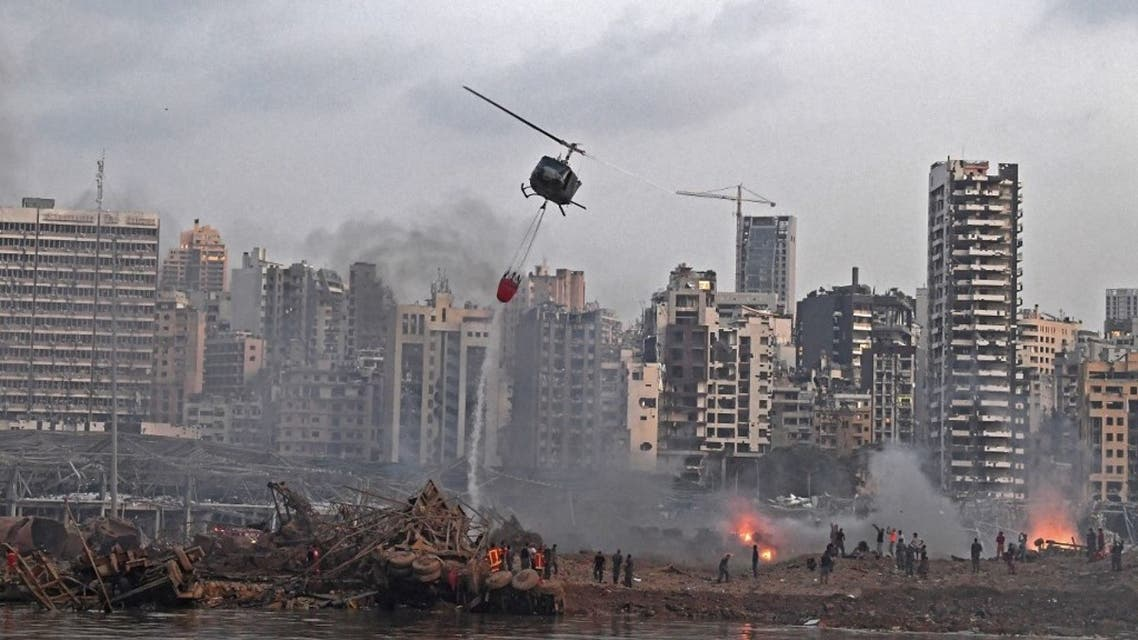 A helicopter try to put out multiple fires at the scene of the massive explosion that hit Beirut's port on August 4, 2020 in the heart of the Lebanese capital.  (AFP)