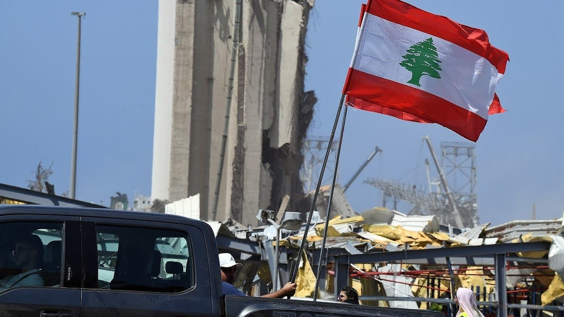Lebanese people carry the national flag as they drive past the blast site in the capital Beirut on August 8, 2020. (AFP)
