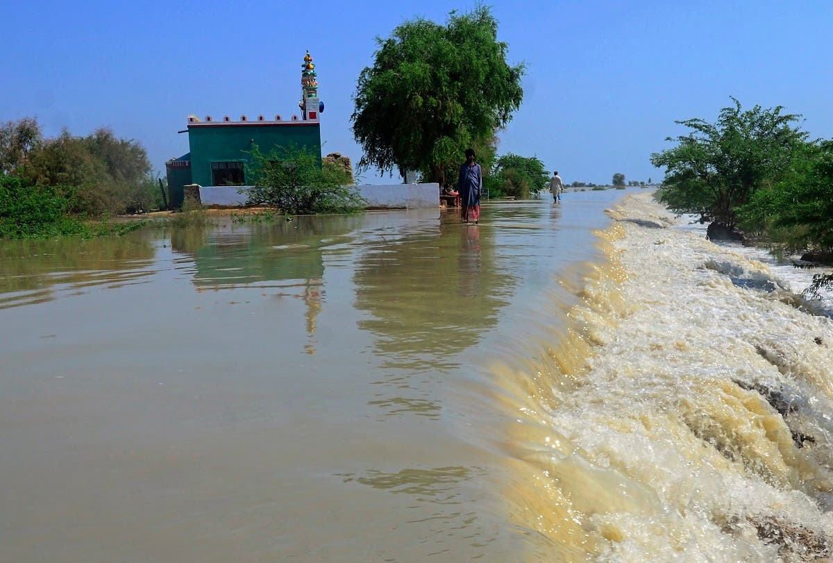 Villagers wade through a flooded area of Dadu, a district in Pakistan's southern Sindh province, on August 9, 2020. (AP)