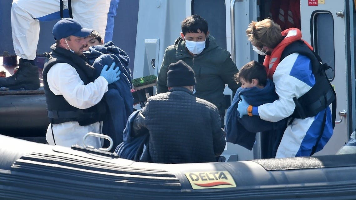 """000_1WE2CXUK Border Force officers help migrants with children, believed to have been picked up from boats in the Channel, disembark from Coastal patrol vessel """"HMC Hunter,"""" in the port of Dover, on the south-east coast of England on August 9, 2020. (AFP)"""