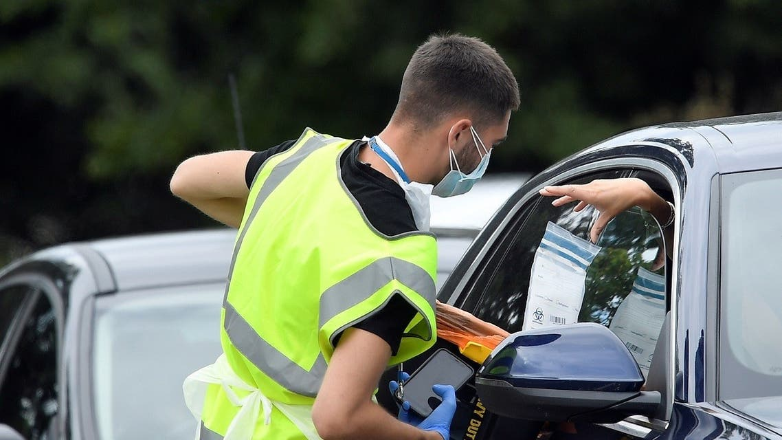 An official delivers a testing kit through a car window at a mobile drive through coronavirus disease (COVID-19) testing centre, in Richmond, London, Britain August 4, 2020. (Reuters)