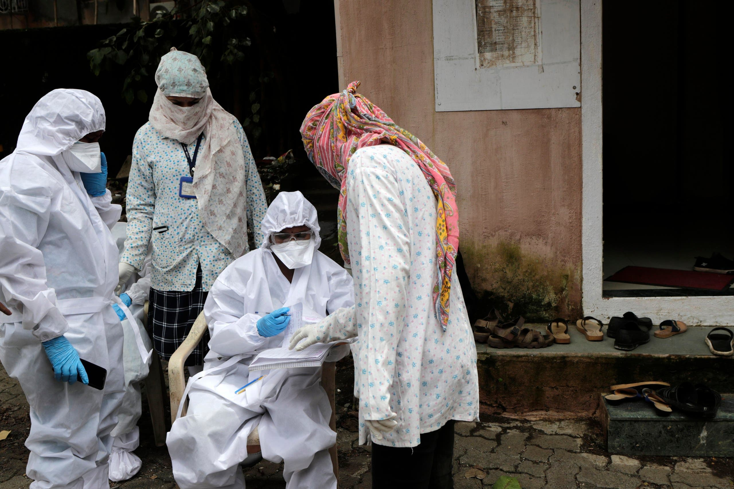 A health worker waits to take nasal swab samples to test for COVID-19 at a medical camp in Mumbai. (AP)