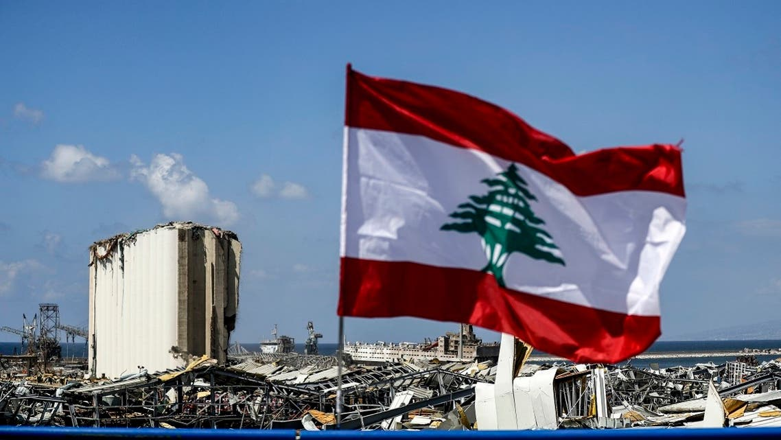 This picture taken on August 9, 2020 shows a Lebanese flag flying along a bridge near the port of Lebanon's capital Beirut, while in the background are seen the damaged grain silos opposite the blast site of a colossal explosion due to a huge pile of ammonium nitrate that had languished for years at a port warehouse. (AFP)