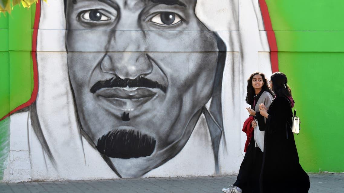 Saudi women walk past a mural painting showing King Salman bin Abdulaziz on Tahliya street in the capital Riyadh on December 5, 2019. (AFP)