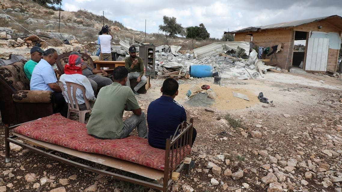 Palestinians sit near the remains of a demolished house on August 10, 2020 near Jenin in the occupied northern West Bank village of Farasi. (AFP)