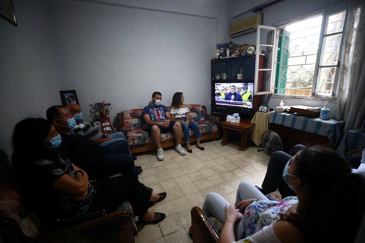 Family members of Ghassan Hasrouty, a missing silo employee, watch a news channel on television as they wait for information, following Tuesday's blast in Beirut's port area. (Reuters)