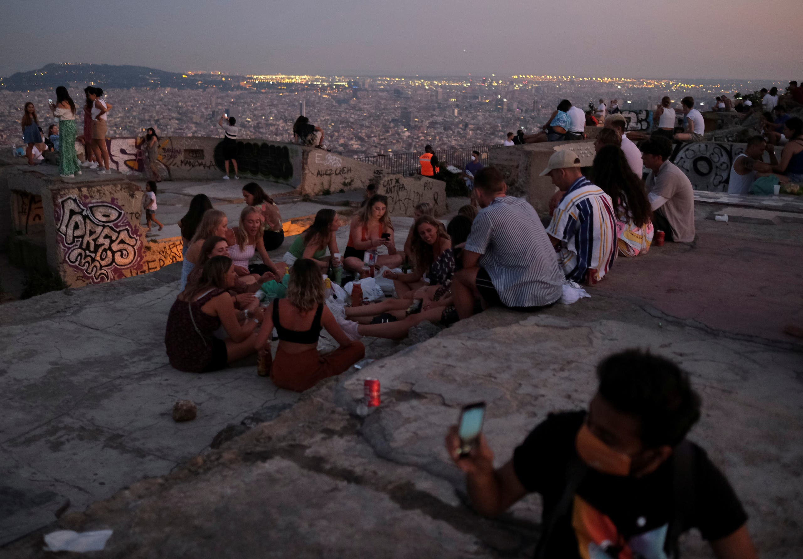 Tourists and locals gather at a lookout point, with a view of the city of Barcelona . (Reuters)
