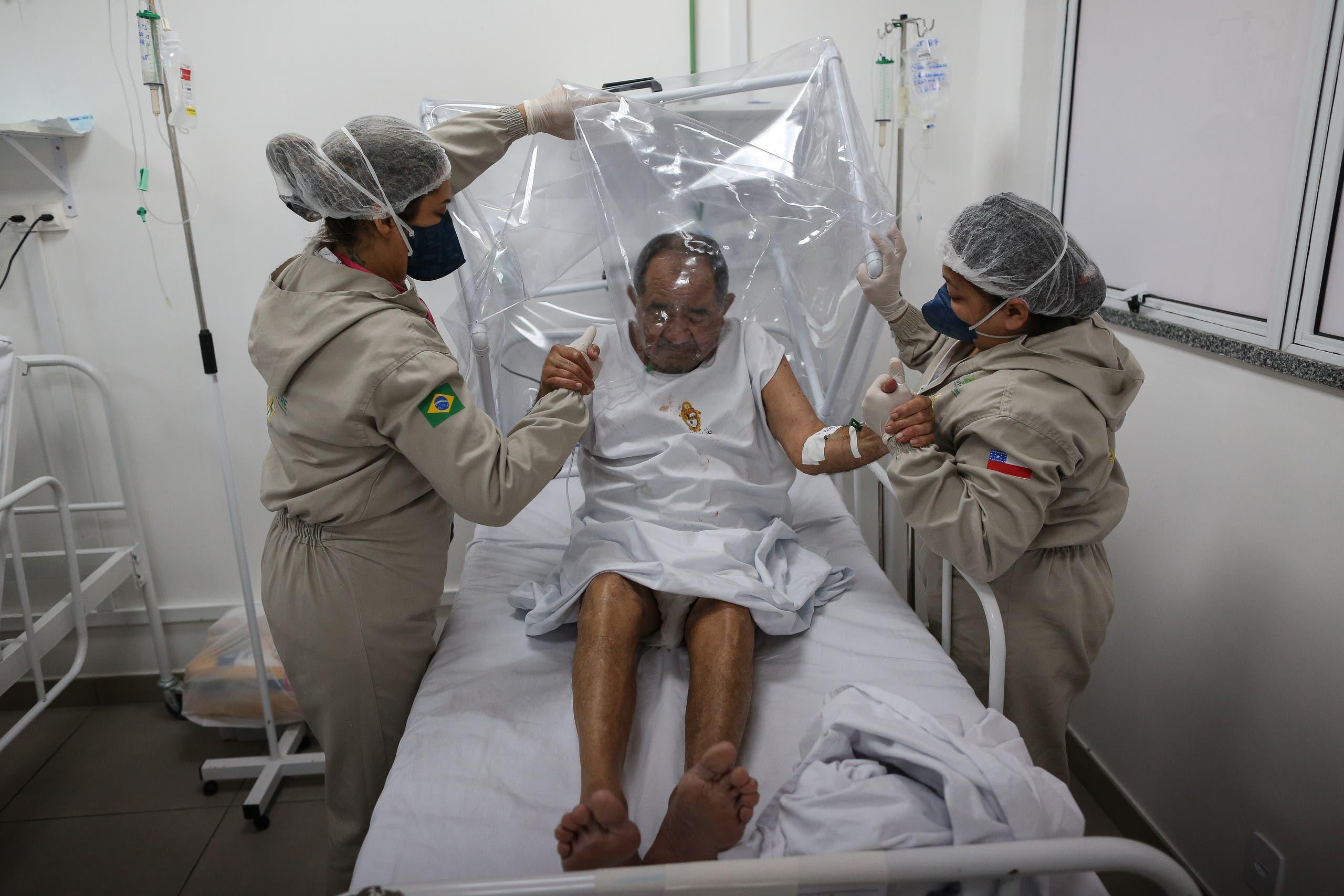 ممرضتان تعتنيان بمصاب بكورونا في البرازيل