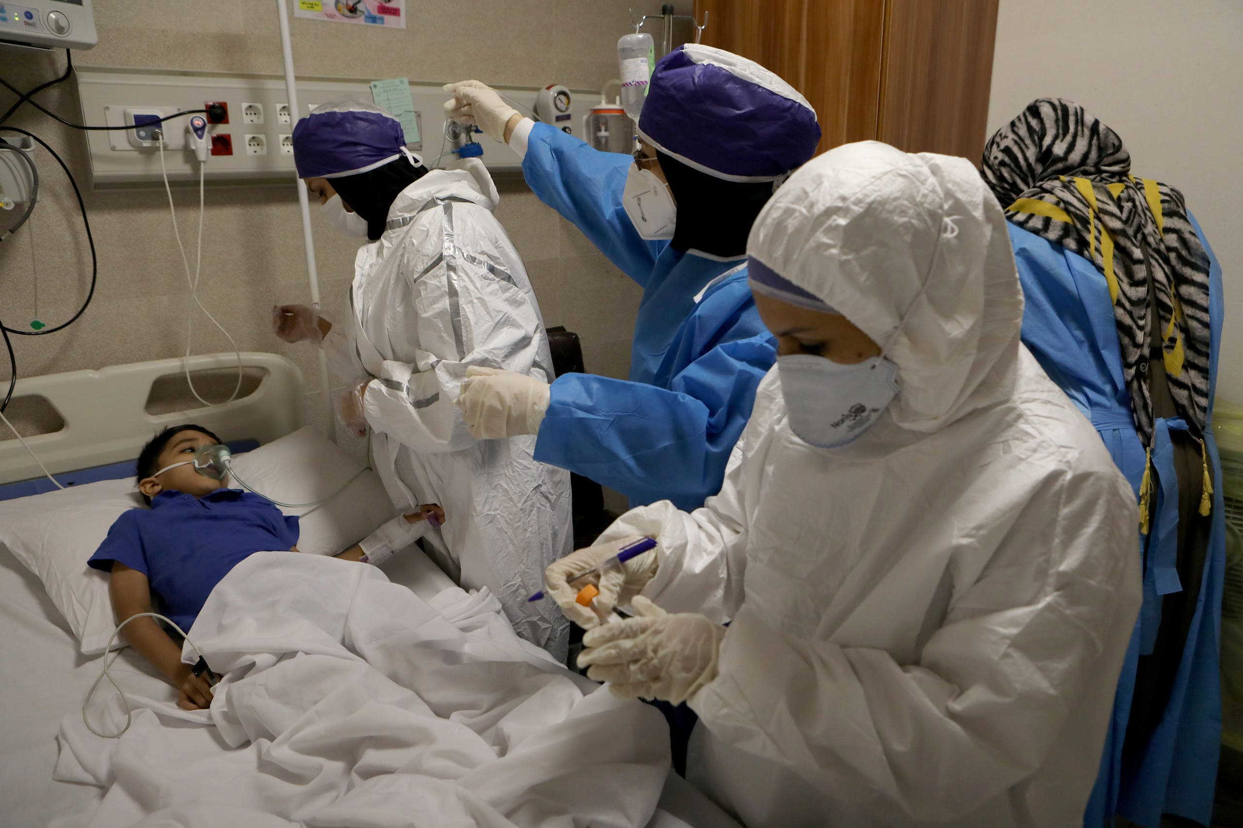 Nurses take a sample from Parham, a 7-year-old, to test for the coronavirus disease (COVID-19), at a hospital, in Tehran, Iran, July 8, 2020. (Reuters)