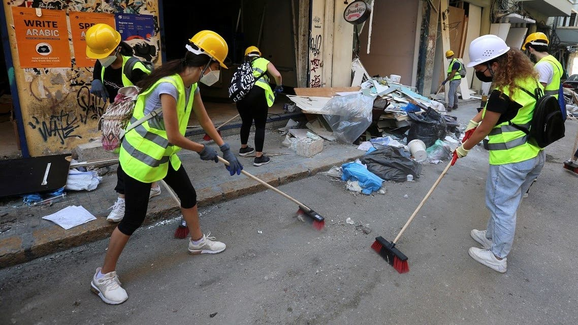 Volunteers clean debris from the street following Tuesday's blast in Beirut's port area. (Reuters)