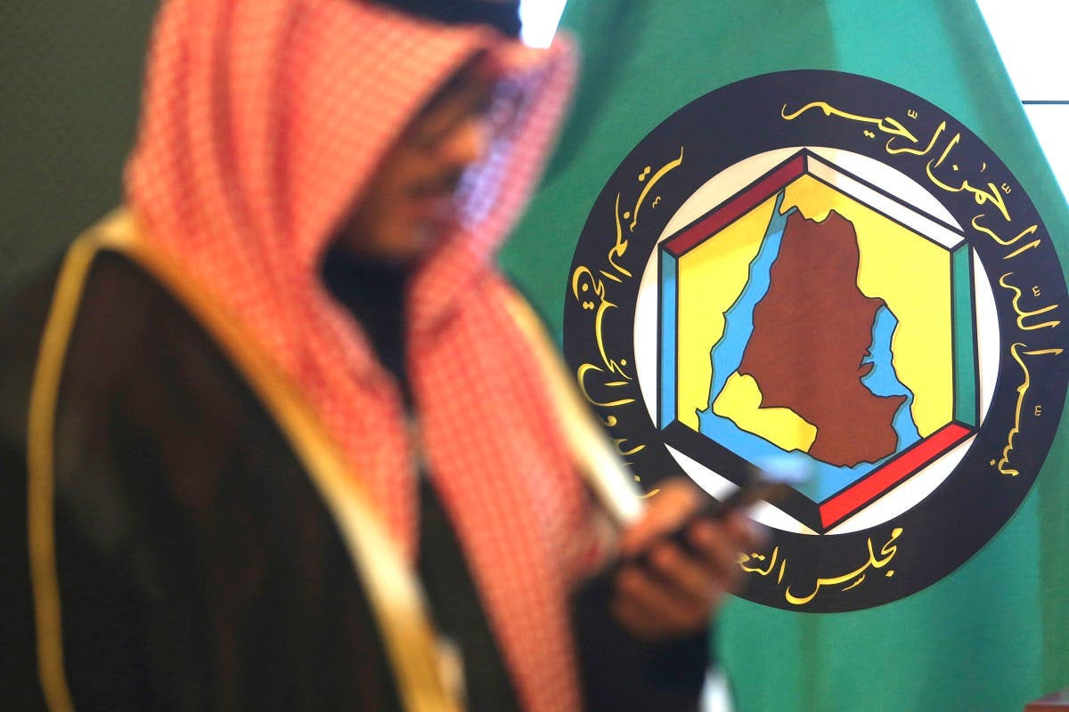 A man looks at his mobile phone in front of the flag of the Gulf Cooperation Council, GCC, in Kuwait City. (File photo: AP)