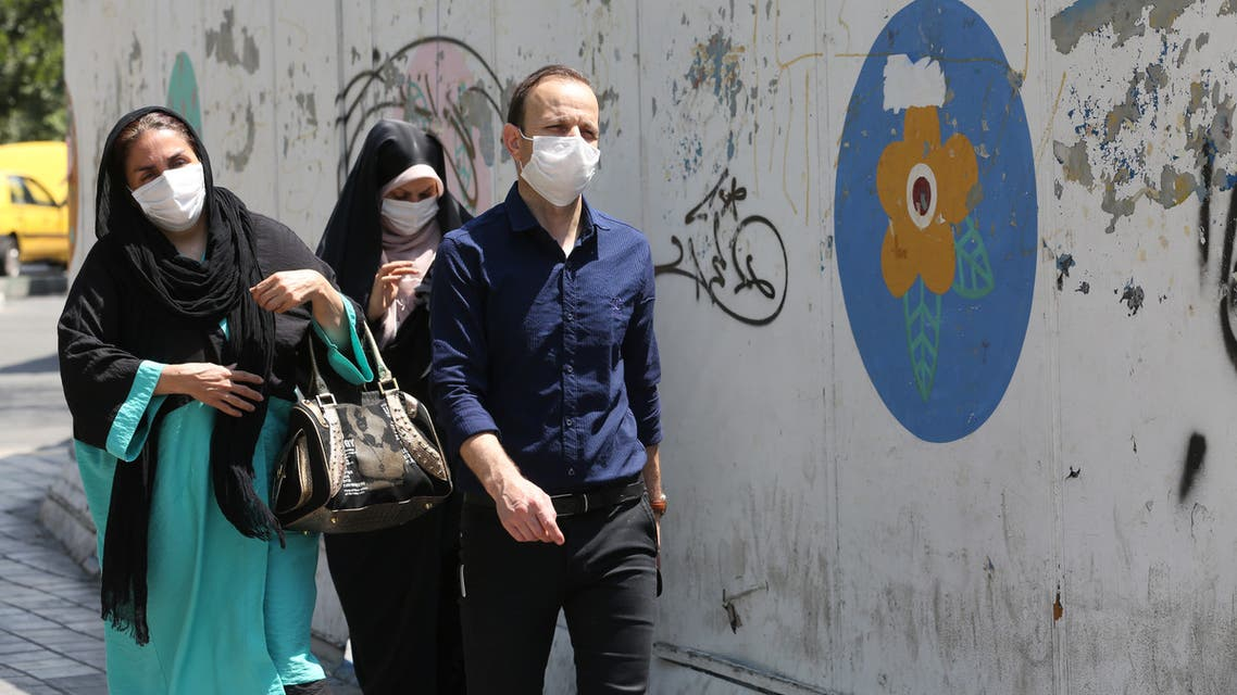 Iranians wearing face masks walk down a street in the capital Tehran amid the novel coronavirus pandemic on August 9, 2020.