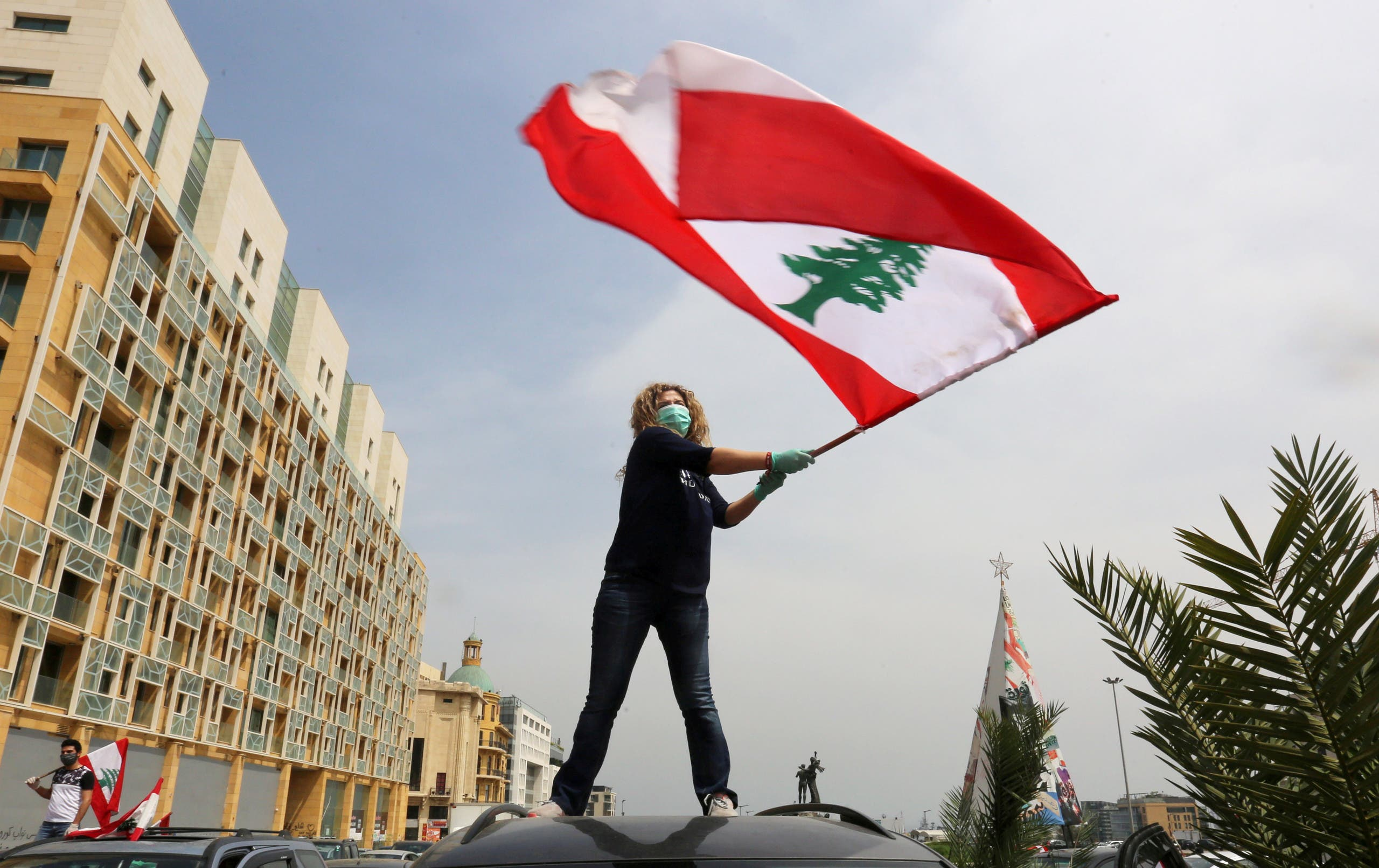 An anti-government demonstrator holds a Lebanese flag as she stands on top of her car in Beirut. (Reuters)