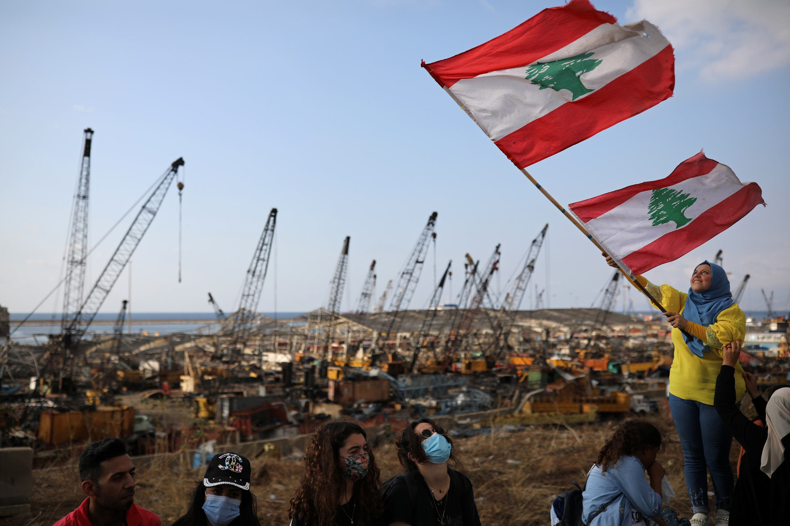 A demonstrator waves the Lebanese flag during protests near the site of the blast at the Beirut's port area on August 11, 2020. (Reuters)