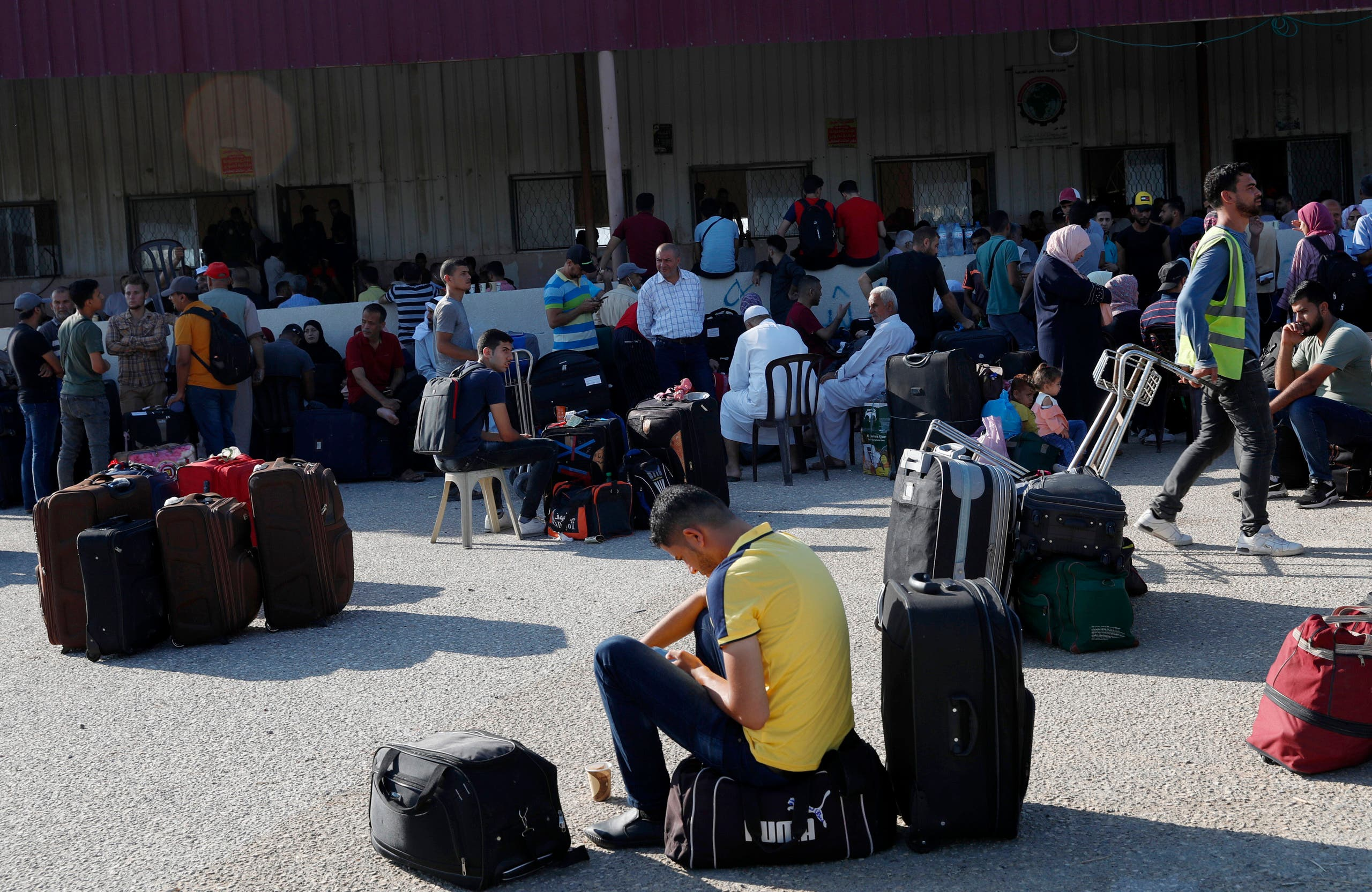 Passengers sit next to their luggage as they wait to cross the border to the Egyptian side of Rafah crossing, in Rafah, Gaza Strip, Tuesday, Aug. 11, 2020. (AP)