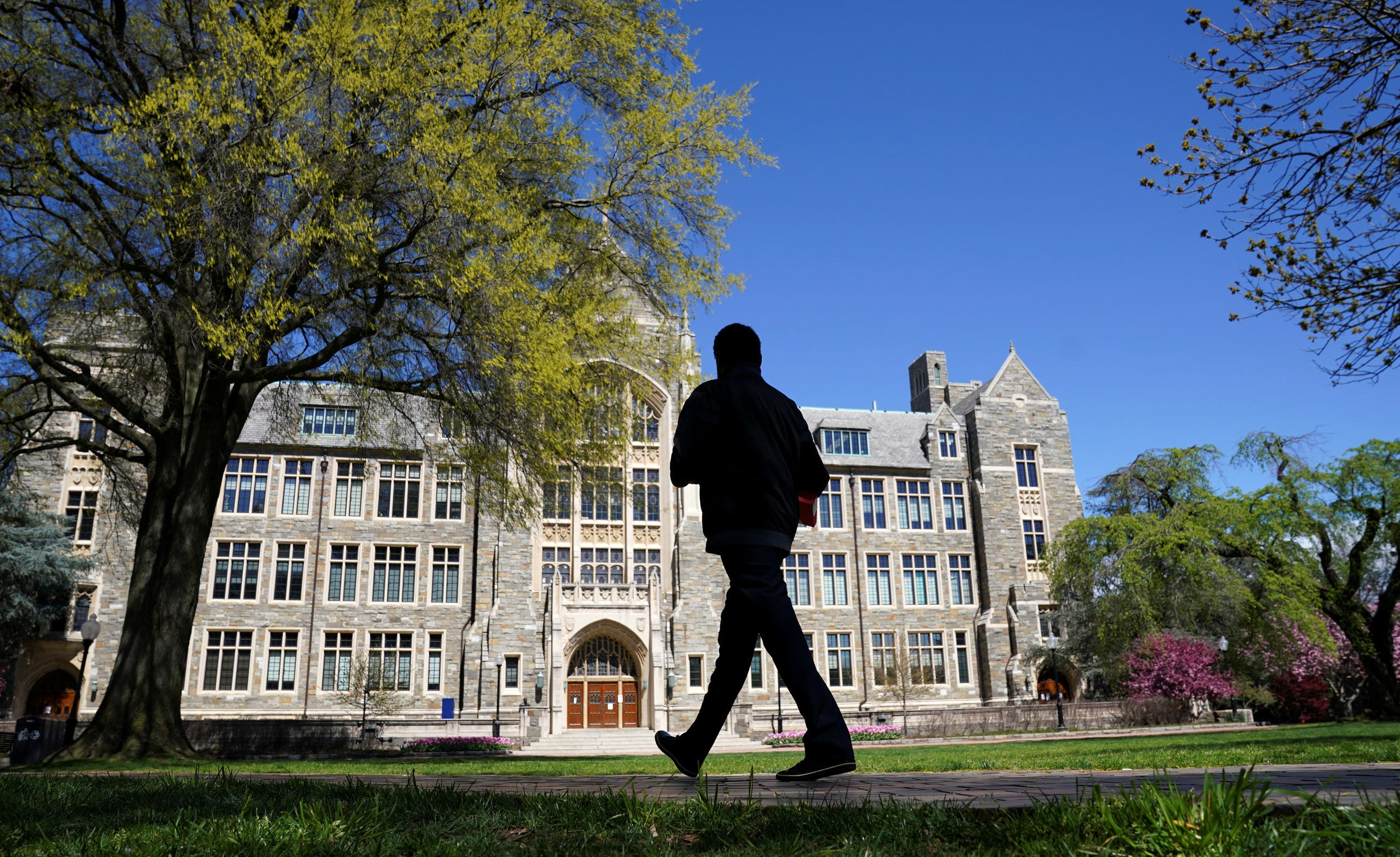 A man walks at an empty campus green at Georgetown University, closed weeks ago due to coronavirus, in Washington on April 3, 2020. (Reuters)