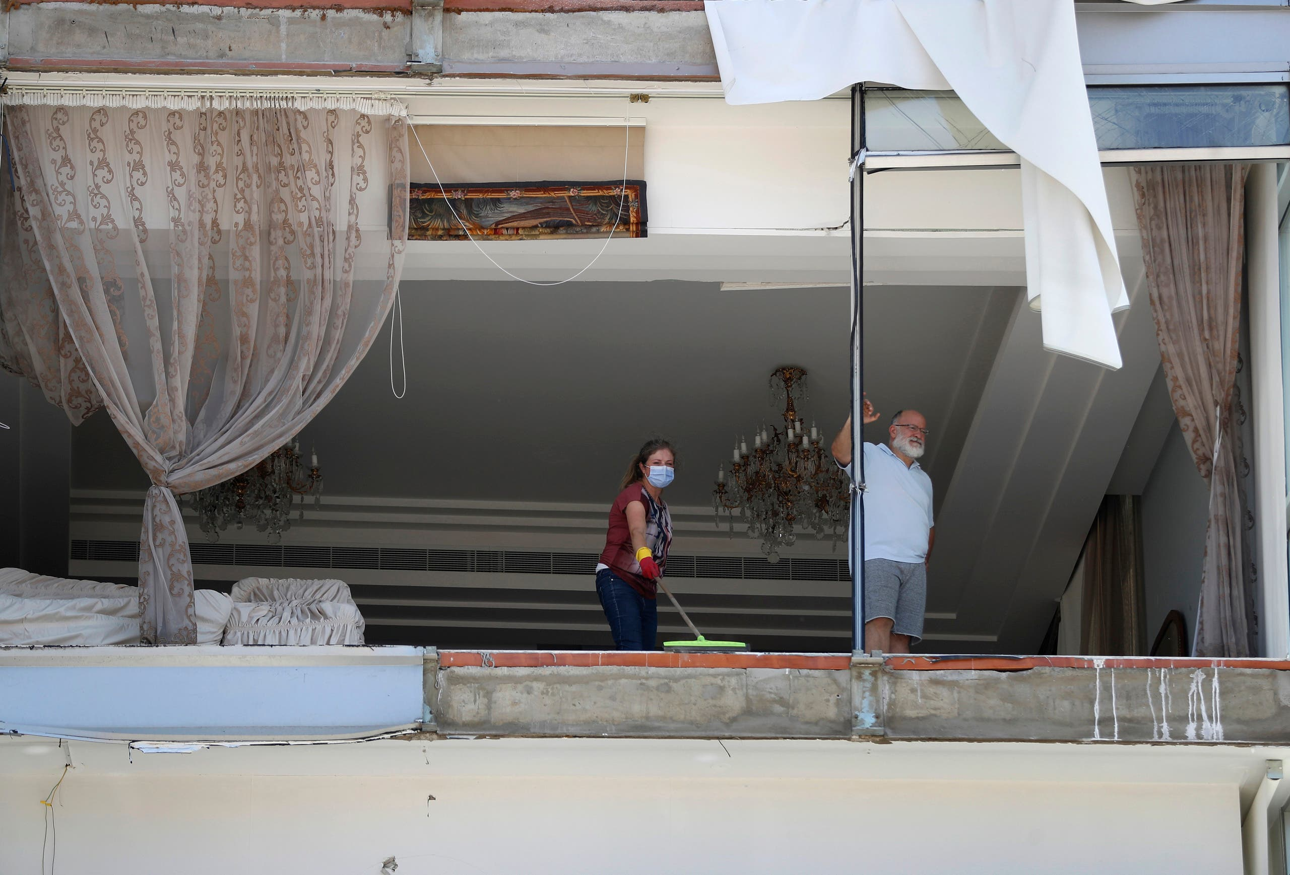 A woman cleans debris from her damaged apartment a day after an explosion hit the seaport of Beirut on Aug. 5, 2020. (AP)