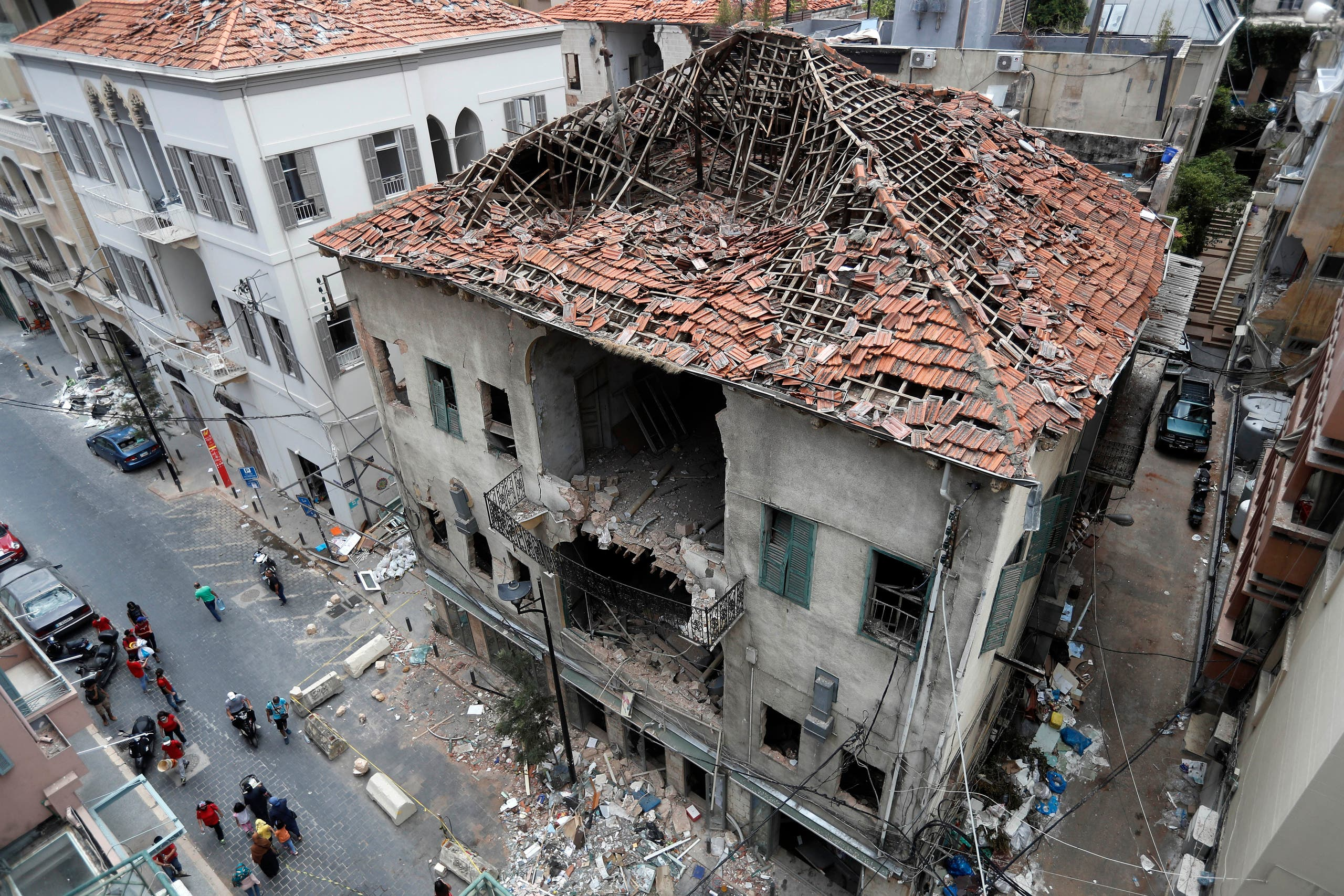 People pass in front of a house that was damaged during the last week's explosion that hit the seaport of Beirut on Aug. 11, 2020. (AP)