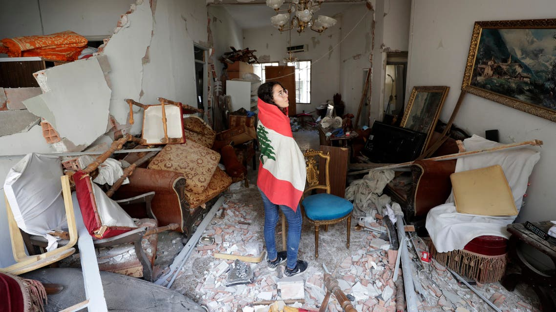 Farah Mahmoud, wrapped in Lebanese national flag, checks her parents destroyed apartment after Tuesday's explosion in the seaport of Beirut on Aug. 6, 2020. (AP)