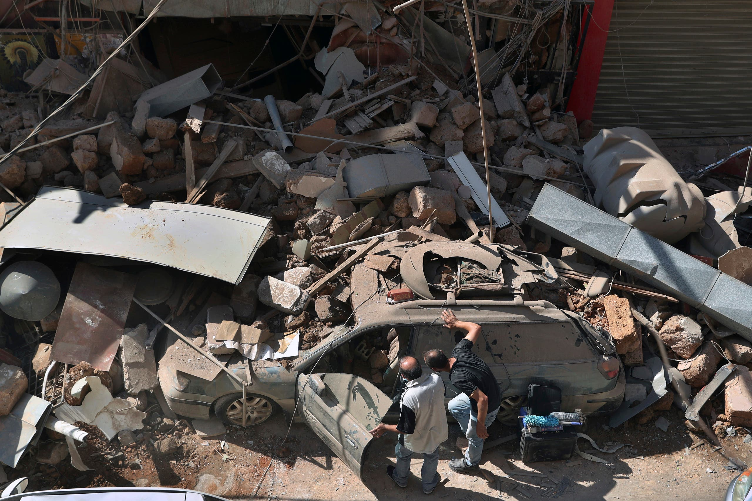 People inspect their car that was damaged in Tuesday's massive explosion in the seaport of Beirut on Aug. 5, 2020. (AP)