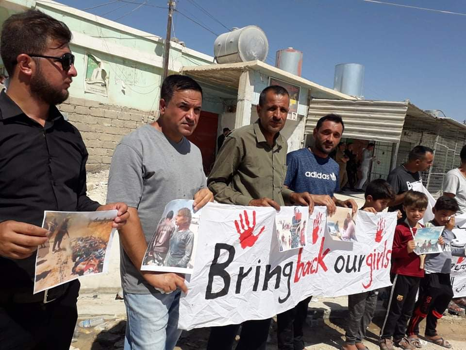 Yazidi men hold up a sign Bring back our girls. (Naji Khadida)