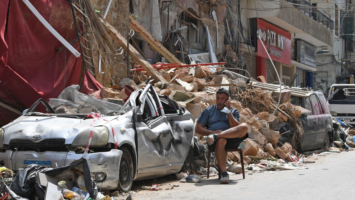 A Lebanese man talks on the phone while seated by the rubble of a destroyed traditional building in the Gemmayzeh neighbourhood, on August 12, 2020, following last week's cataclysmic port explosion which devastated the capital Beirut.