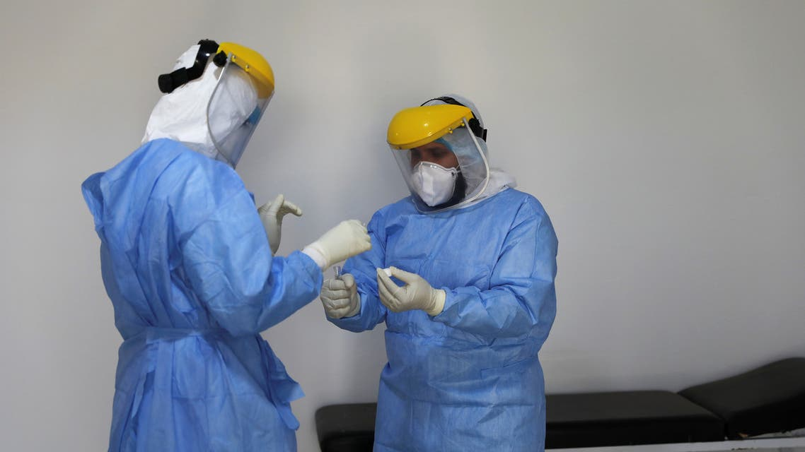 A member of a medical team wearing a protective suit carries a test tube after taking a swab from a man to test for the coronavirus disease (COVID-19), at a medical clinic in Tripoli, Libya June 10, 2020. REUTERS/Ismail Zitouny