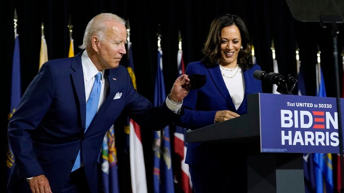 Democratic presidential candidate Joe Biden gets his face mask from the podium before his running mate Kamala Harris speaks during a campaign event, Aug. 12, 2020. (AP)