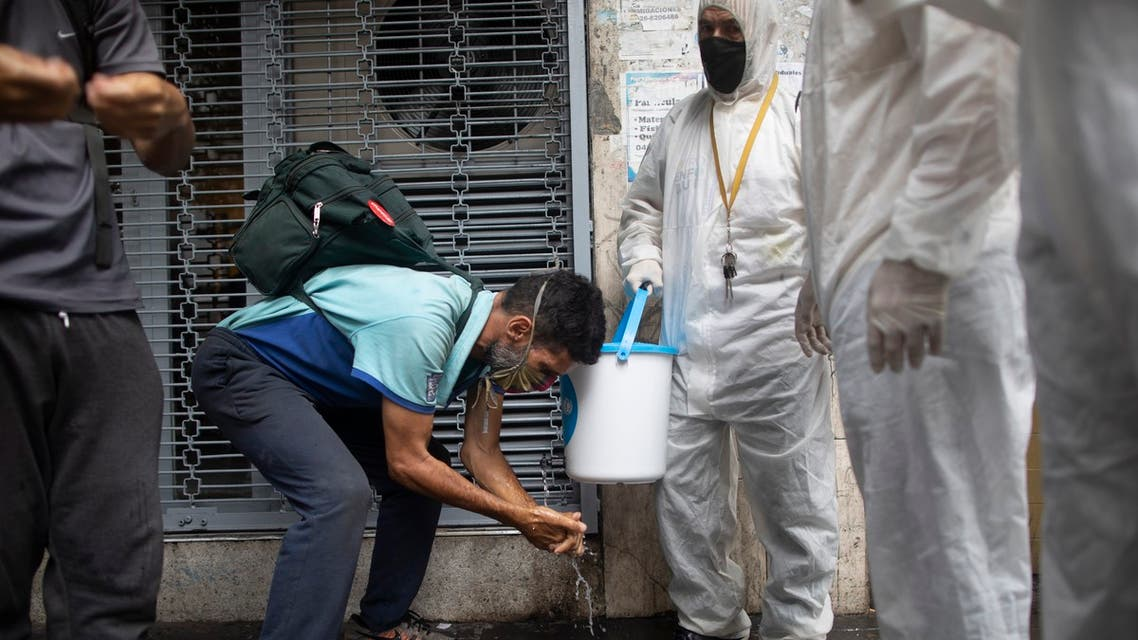 Members of the Another Approach non-governmental organization teach residents how to correctly wash their hands amid the new coronavirus pandemic, on a street in Caracas, Venezuela, Tuesday, July 21, 2020. (AP)