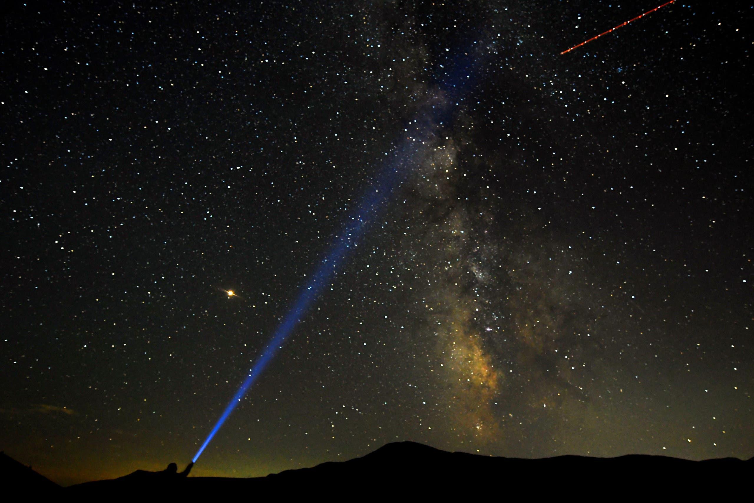 رجل يشير بضوء إلى درب التبانة في سماء مقدونيا في صيف 2018
