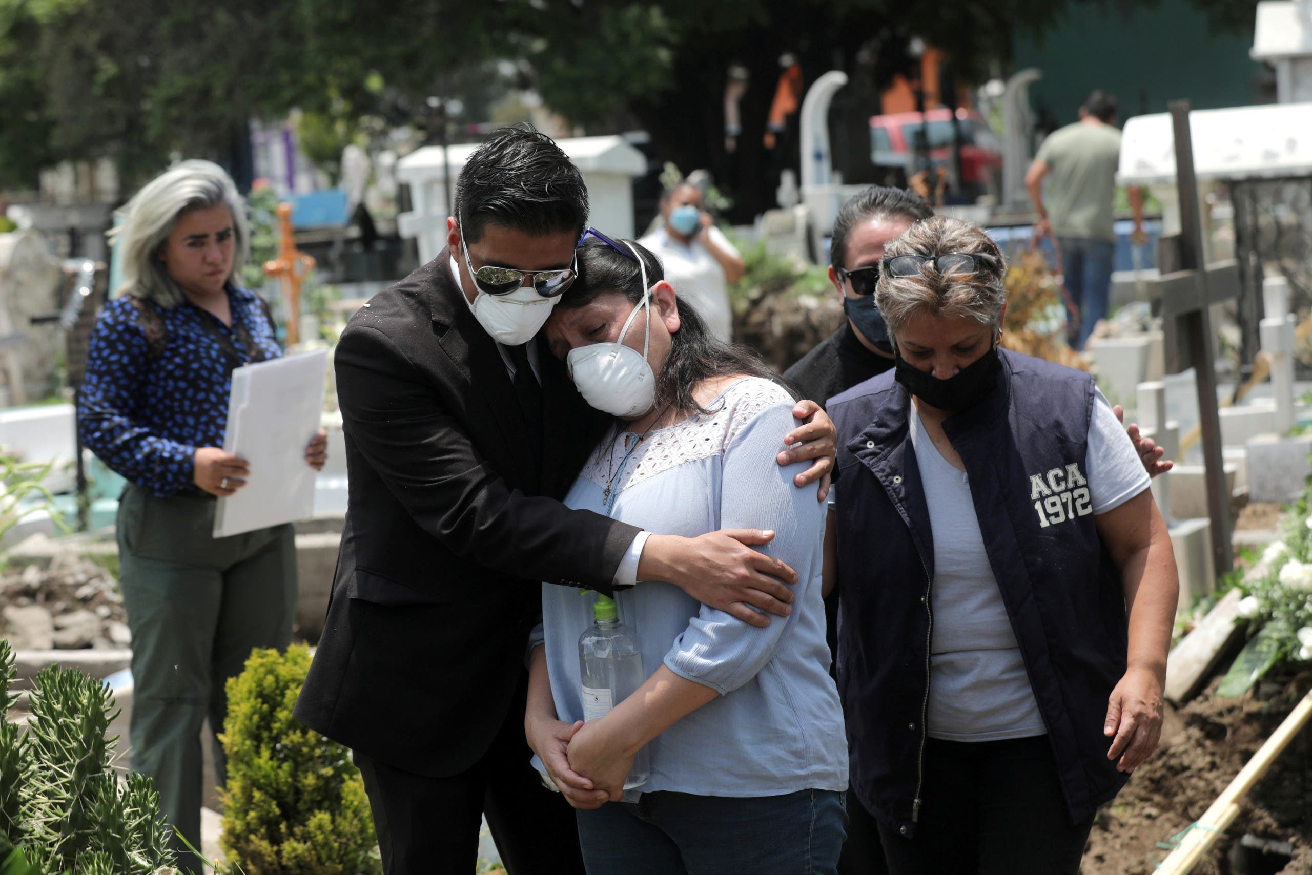Relatives react near the coffin of a man, during his funeral at the local cemetery, as the coronavirus disease (COVID-19) outbreak continues in Mexico City, Mexico, August 6, 2020. (Reuters)