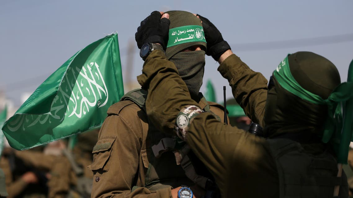 A Palestinian Hamas militant adjusts the mask and headband of his comrade during an anti-Israel military show in the southern Gaza Strip November 11, 2019. REUTERS/Ibraheem Abu Mustafa