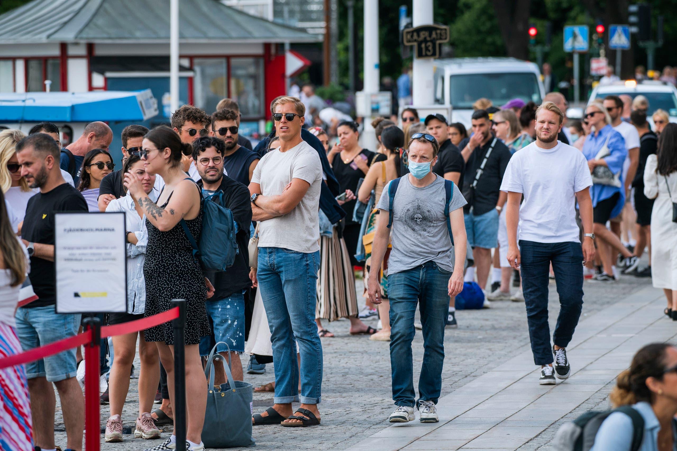 رجل يرتدي الكمامة وحيداً وسط مسافرين ينتظرون للركوب على متن إحدى السفن في السويد في يوليو الماضي