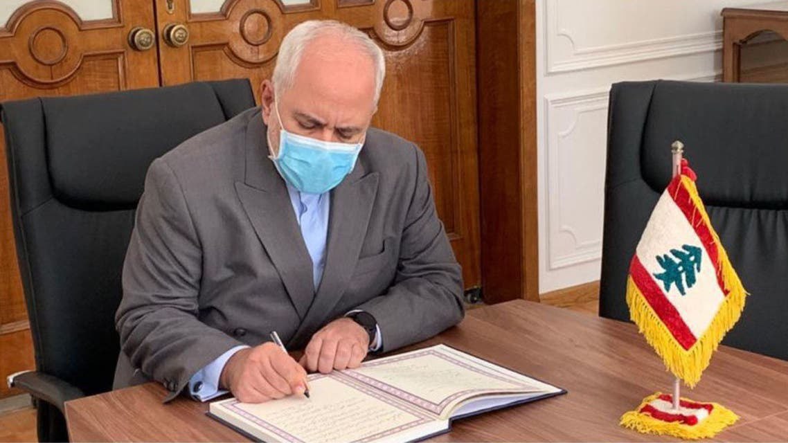 A handout picture provided by the Iranian Foreign Ministry on August 9, 2020 shows Foreign Minister Mohammad Javad Zarif signing a memorial note for the victims of the blast at the port of Beirut, at the Lebanese embassy headquarters in Iran's capital Tehran.