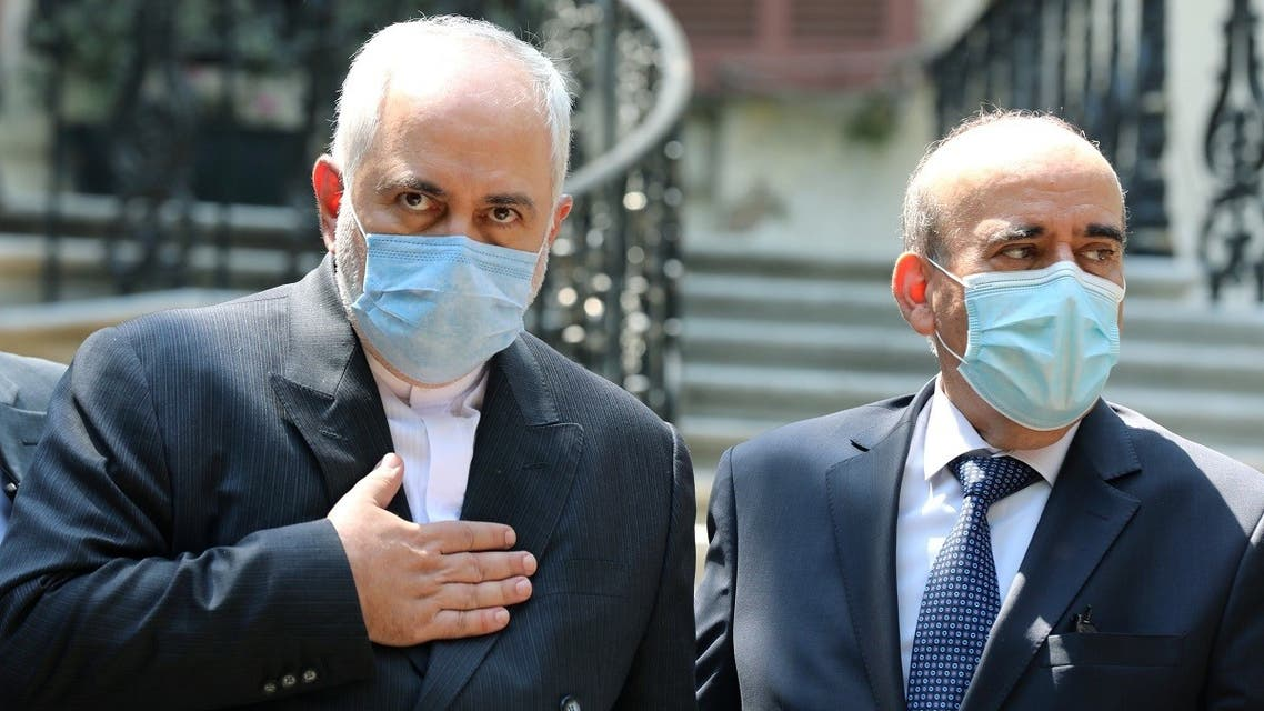Iran's Foreign Minister Mohammad Javad Zarif and Lebanon's caretaker Foreign Minister Charbel Wehbe wear protective face masks as they stand at the Ministry of Foreign Affairs in Beirut. (Reuters)