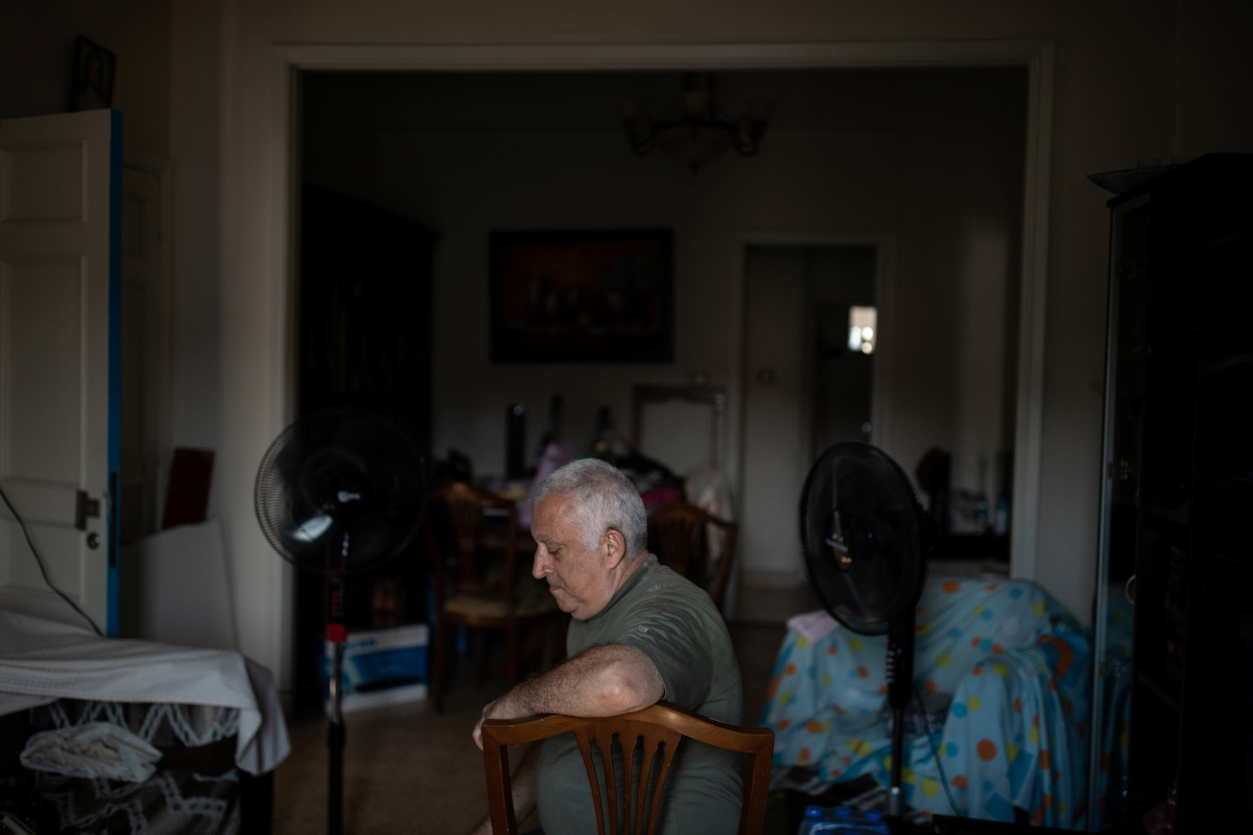 Tony Matar, 68, sits on a chair in his living room at his home that was damaged by an explosion at the Beirut port, in the neighbourhood of Karantina, Beirut. (Reuters)