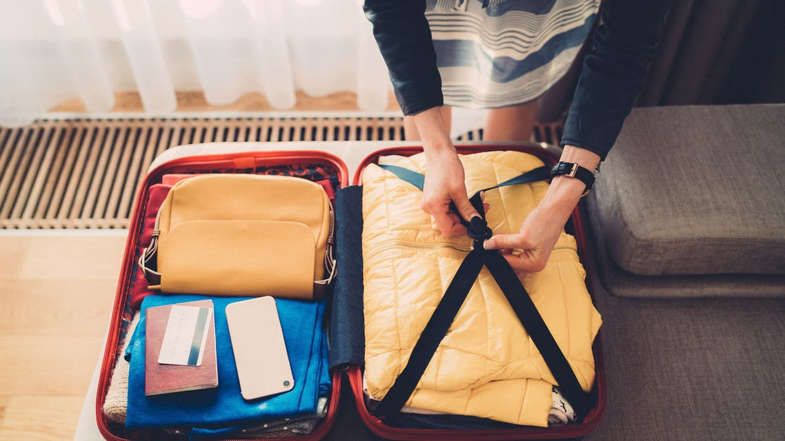 Woman hands packing a luggage for a new journey and travel for a long weekend stock photo