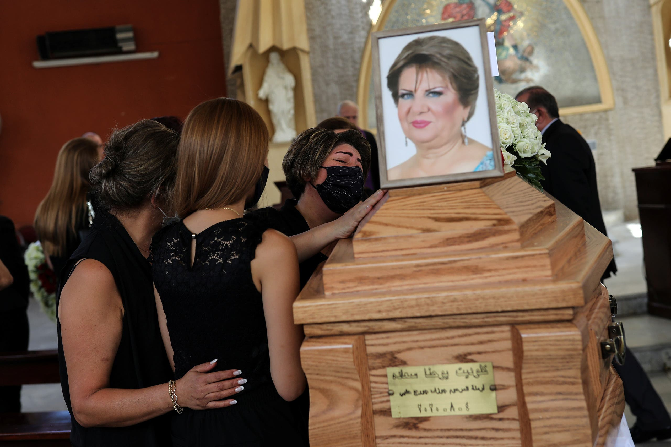 A woman reacts next to a coffin of Claudette Halabi who was killed in an explosion at the Beirut Port, during her funeral procession in Beirut. (Reuters)