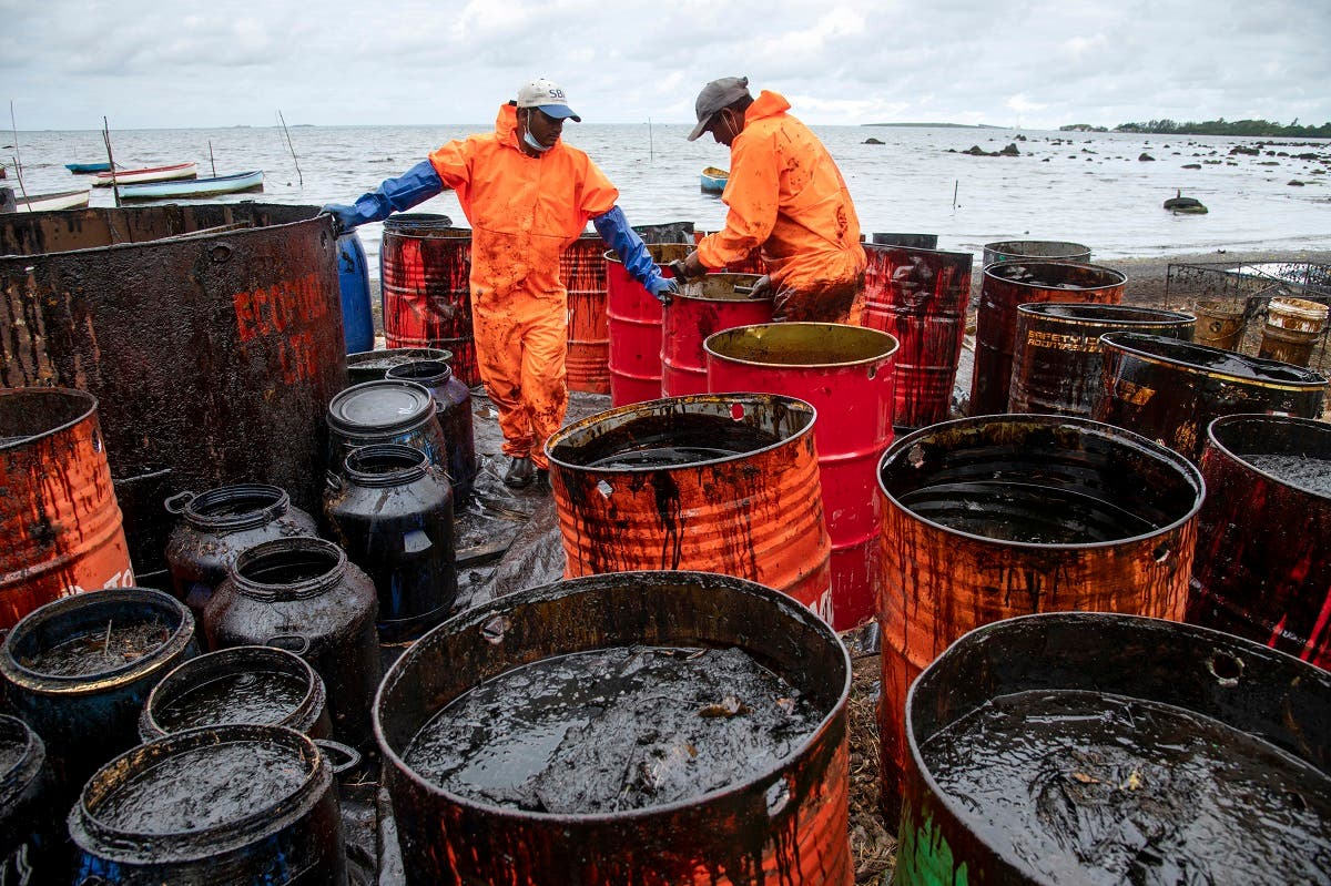 Workers collect leaked oil at the beach in Riviere des Creoles on August 15, 2020, due to the oil leaked from vessel MV Wakashio off the coast of south-east Mauritius. (AFP)