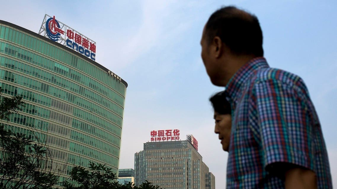 People walk past buildings of China's state-owned companies, China National Offshore Oil Corp. (CNOOC), left, and China Petroleum & Chemical Corp. (Sinopec), in Beijing Monday, Sept. 14, 2015. (AP)